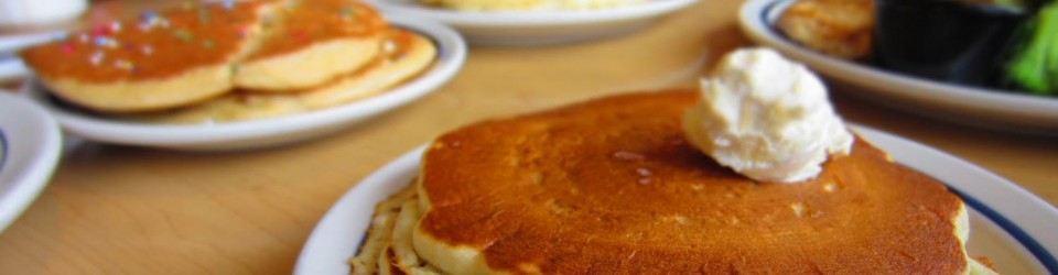 [stack of pancakes with a blob of cream at the foreground; other stacks of out of focus pancakes in the background]