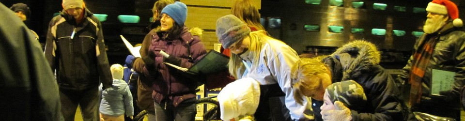[CUMC members singing carols by Naperville Train Station]