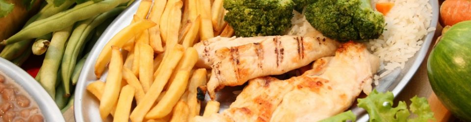 [chicken, fries, broccoli, on a plate surrounded with salad fixings]
